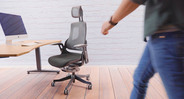 The sleek high-back chair features a slick black frame, charcoal mesh back, a black powder-coated aluminum base