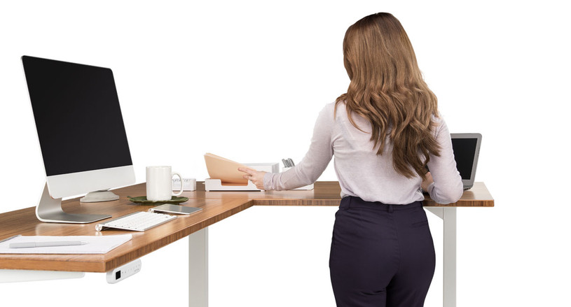 The UPLIFT Height Adjustable Standing Desk with L-Shaped Top is a comfortable fit for your computer, papers, and decor.