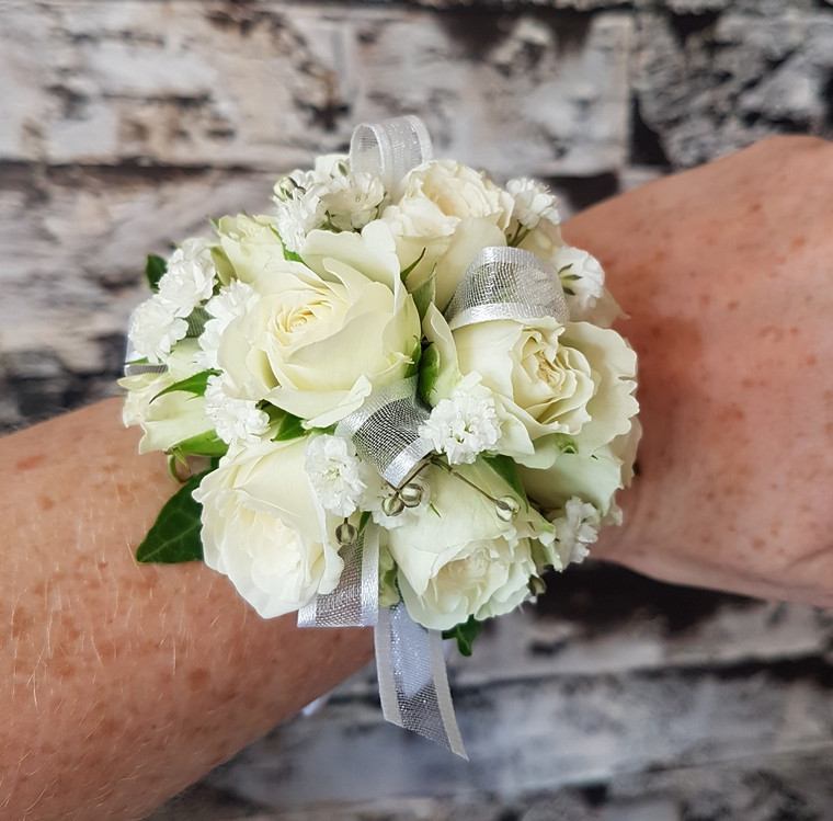 White spray roses and baby's breath corsage with white ribbon