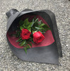Two red roses and seasonal foliage.