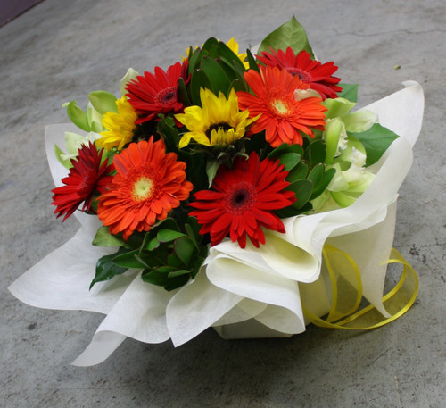 Bright Vibrant reds, oranges in yellows ! Inluding Gerberas and Sunflowers and Lime green accents.