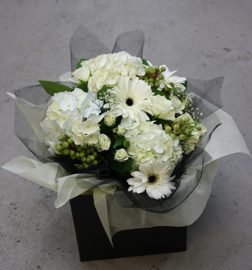 Seasonal White flowers in black and white wrapping, includes hydrangeas, gerberas and lizzianthus.