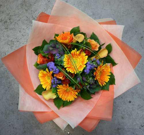 Vibrant bouquet of callas, gerberas, kale, roses and purple acents and seasonal foliage.