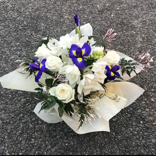 White flower arrangement with a splash of blue, arranged in a posy box.