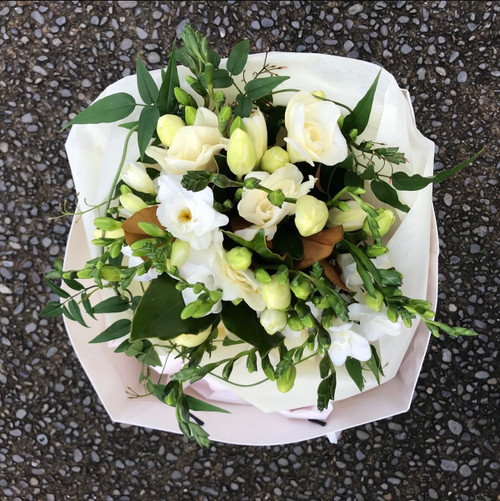 White freesias and seasonal foliages in a white carry bag.