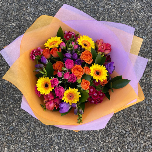 Bright hand tied bouquet of seasonal flowers in bright pinks, yellows, purples and oranges.
