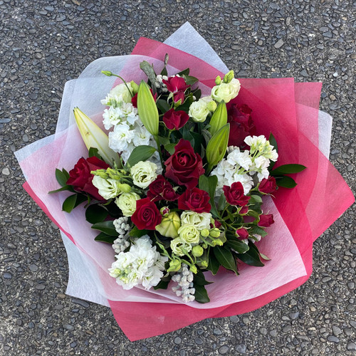 Christmas themed bouquet of whites, greens and reds. includes white lilies and red roses with other seasonal white, red and green blooms.