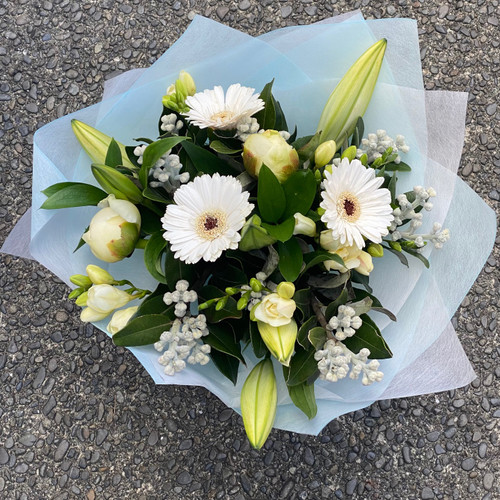 Christmas bouquet in fresh white and green seasonal flowers with assorted foliage.