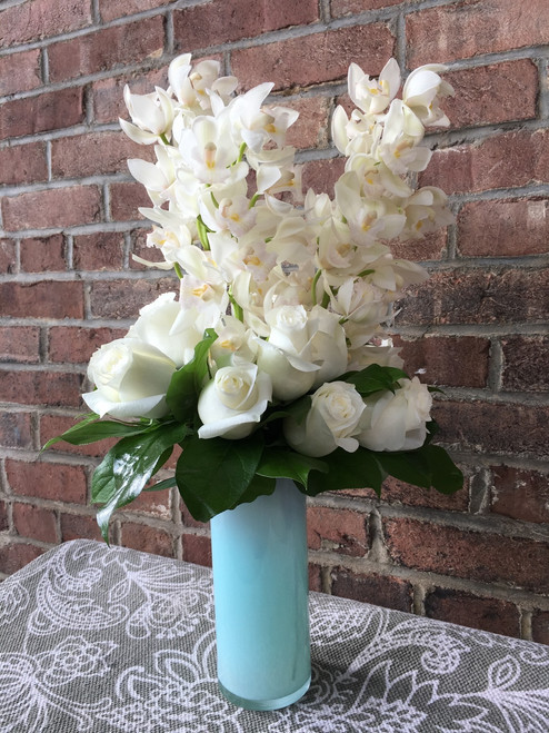 A sultry statement and a vision in cream and pastels - cymbidium and roses in an immaculate frosted vase.  Colors vary, contact shop for specific colors.