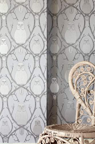 Owls sitting on branches in silver metallic wallpaper designed by Abigail Edwards.