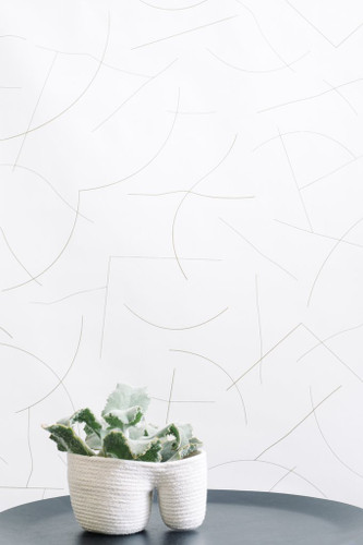 Abstract lines in silver on cream wallpaper.