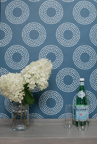 Indigo wallpaper with organic spots in a circle pattern in white.