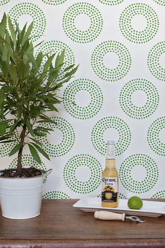 Grassy green organic spots in a circle pattern on a white wallpaper.