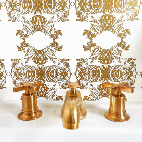 Tiger heads that form a lace patterned wallpaper in metallic gold.