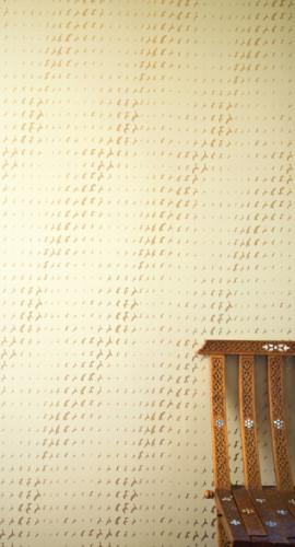Gold birds in a flight pattern on wallpaper.