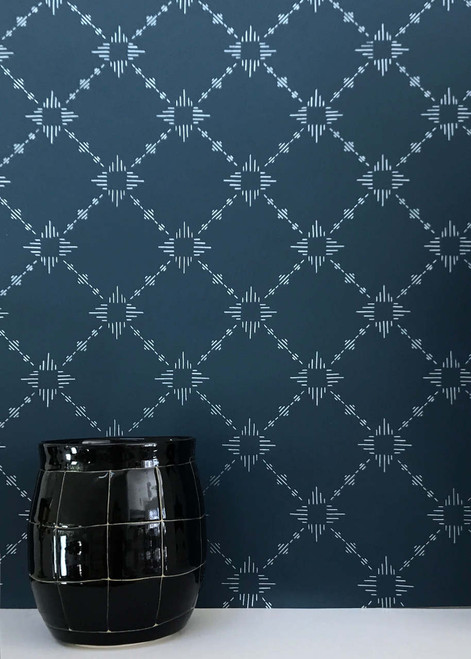 Silver metallic on a deep blue wallpaper in a diamond pattern with bursts.