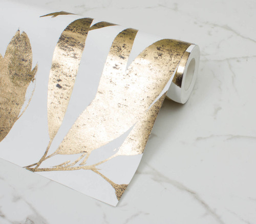 Gold foil wallpaper on a white background with oversized eucalyptus leaves.