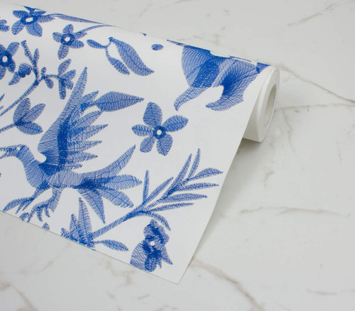 Navy stitching on white wallpaper in a Otomi pattern.