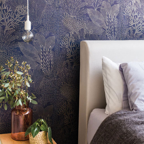 Bedroom with navy and gold wallpaper.