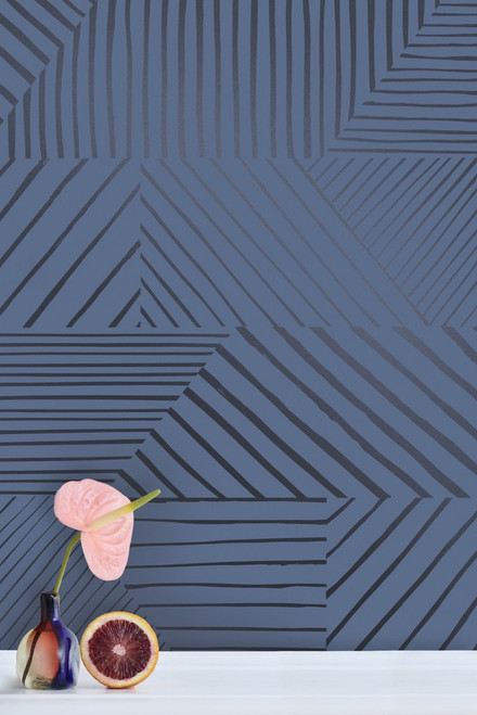 A collage of charcoal stripes, puzzled together in an asymmetrical pattern on navy wallpaper.