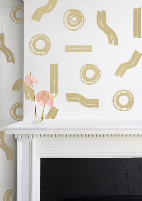 Artfully arranged gold circles and line on this cream wallpaper.