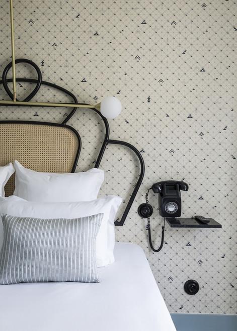 Bedroom with geometric wallpaper pattern.