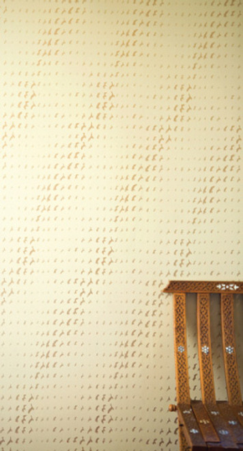 Gold birds in a flight pattern on wallpaper.