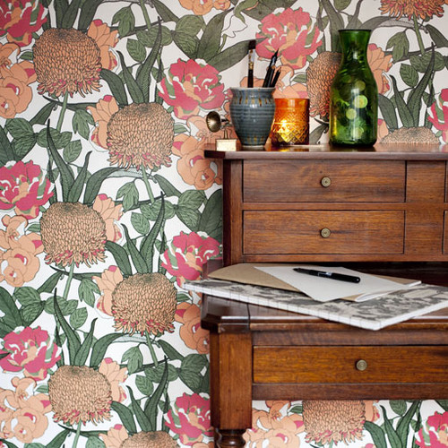 Climbing foliage set amongst Chrysanthemums and Peonies on this orange and green wallpaper.