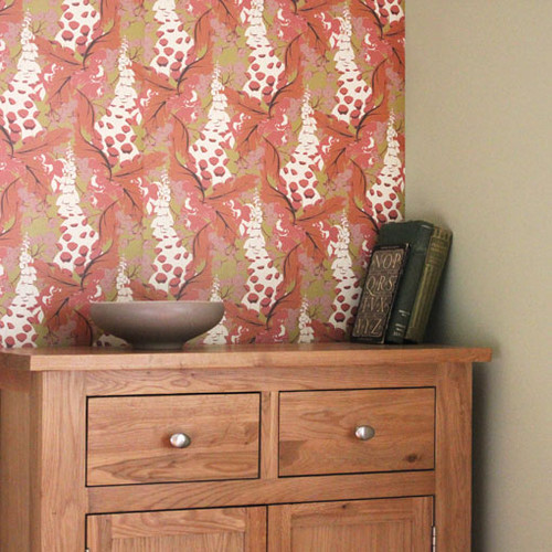 Leaves wrap around Foxgloves and small blossoms on this warm orange floral wallpaper.