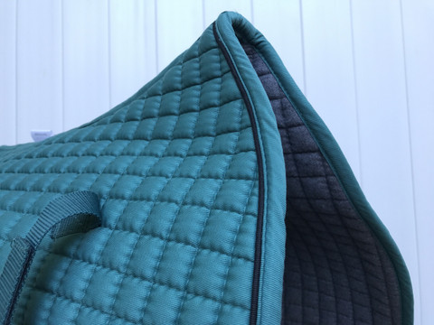 Zoom to view this pine forest green dressage saddle pad with black piping.