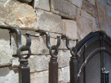 Wrought iron fire tool hooks installed into masonry