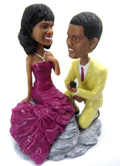 Custom proposal wedding cake topper is sculpted to look like the bride and groom.