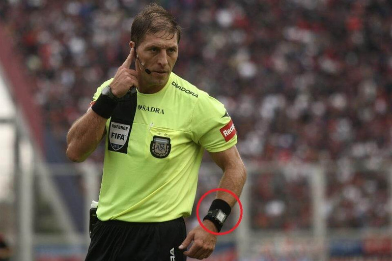 Argentina FIFA Referee Nestor Pitana gestures with his earpiece while wearing the Spintso Referee Pro Watch