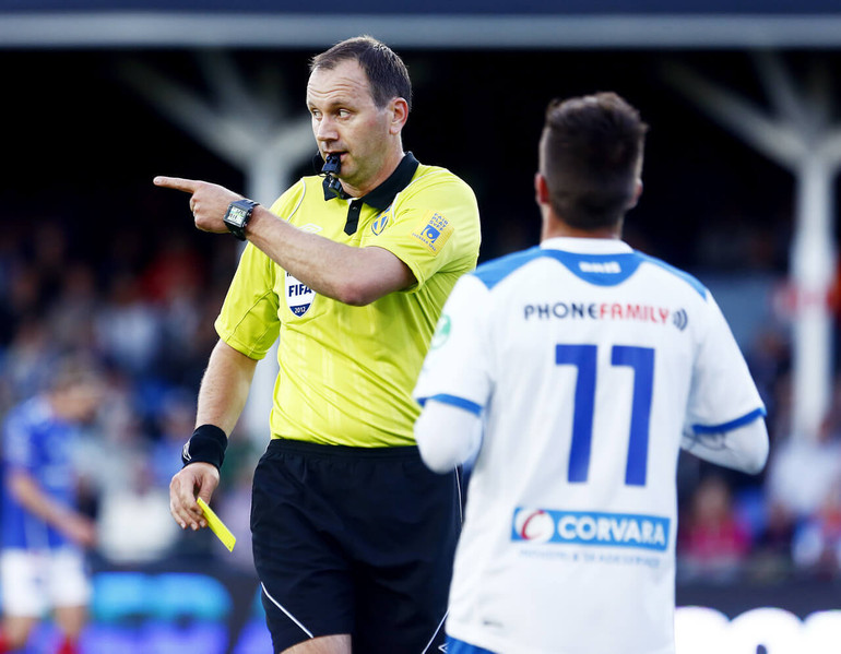 Sweden FIFA Referee Jonas Eriksson points to a player about to receive a yellow card, while wearing the Spintso Referee Pro Watch