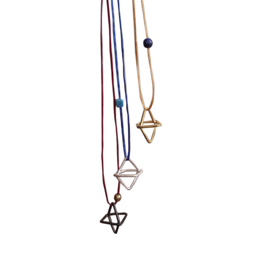 Minimal Geometric small charm necklace hanging from a cord