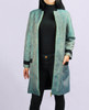 Lagom Imperia Coat front view, worn by model on grey background