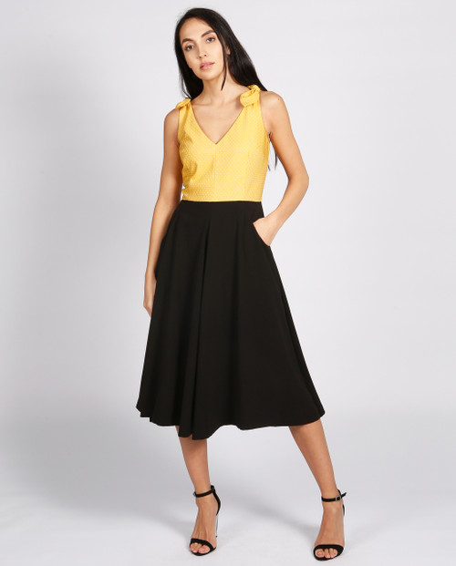 Lagom Bonbon Dress Black-Yellow front view with hand in pocket, worn by model on grey background