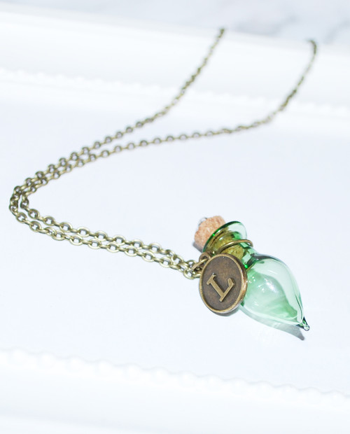 Lagom  Bottle Necklace Green-Bronze side view on grey scalloped background