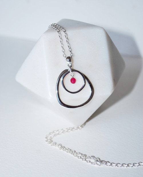Lagom Darcy Circle Necklace Raspberry detailed view draped on white stand