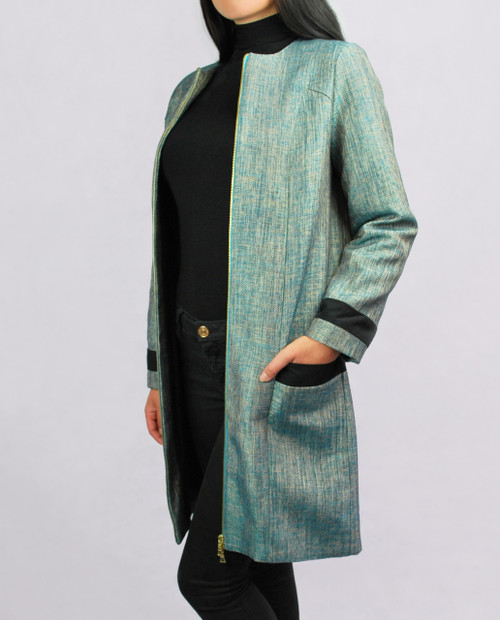 Lagom Imperia Coat side view, worn by model on grey background