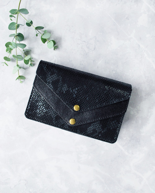 Lagom Kensington Mini Bag Black front view with green sprig on marble background