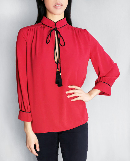 Lagom Elegant Brera Blouse in red crepe fabric with black piping and black rope tassels, £65, front view on model