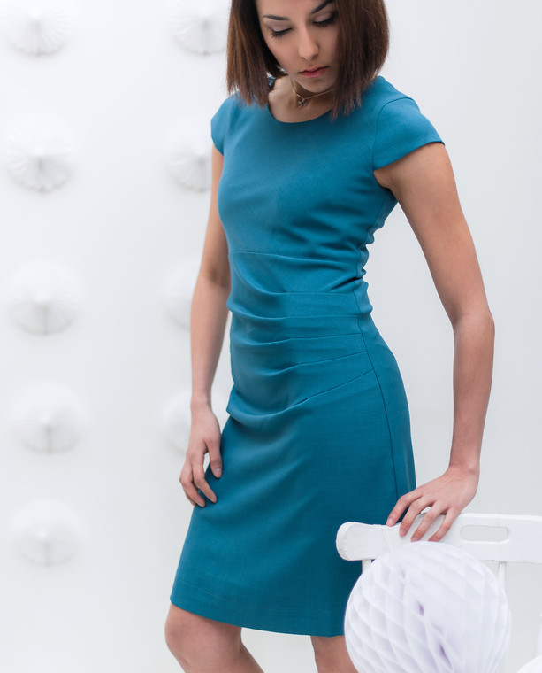 Lagom Bella Dress Teal side view,  worn by model on grey textured background