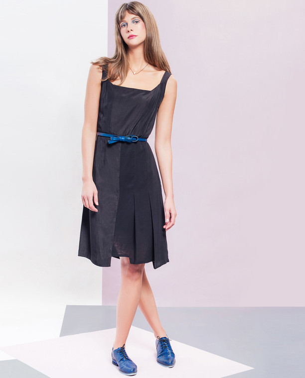 Lagom Chelsea Dress Black front view, worn by model on multi-coloured background