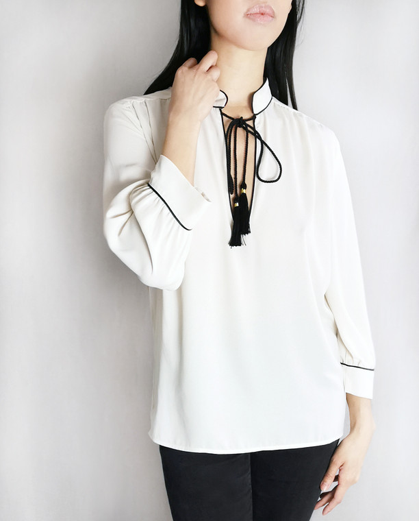 Lagom Brera Blouse in cream crepe fabric with black tassels, £65, front view on model