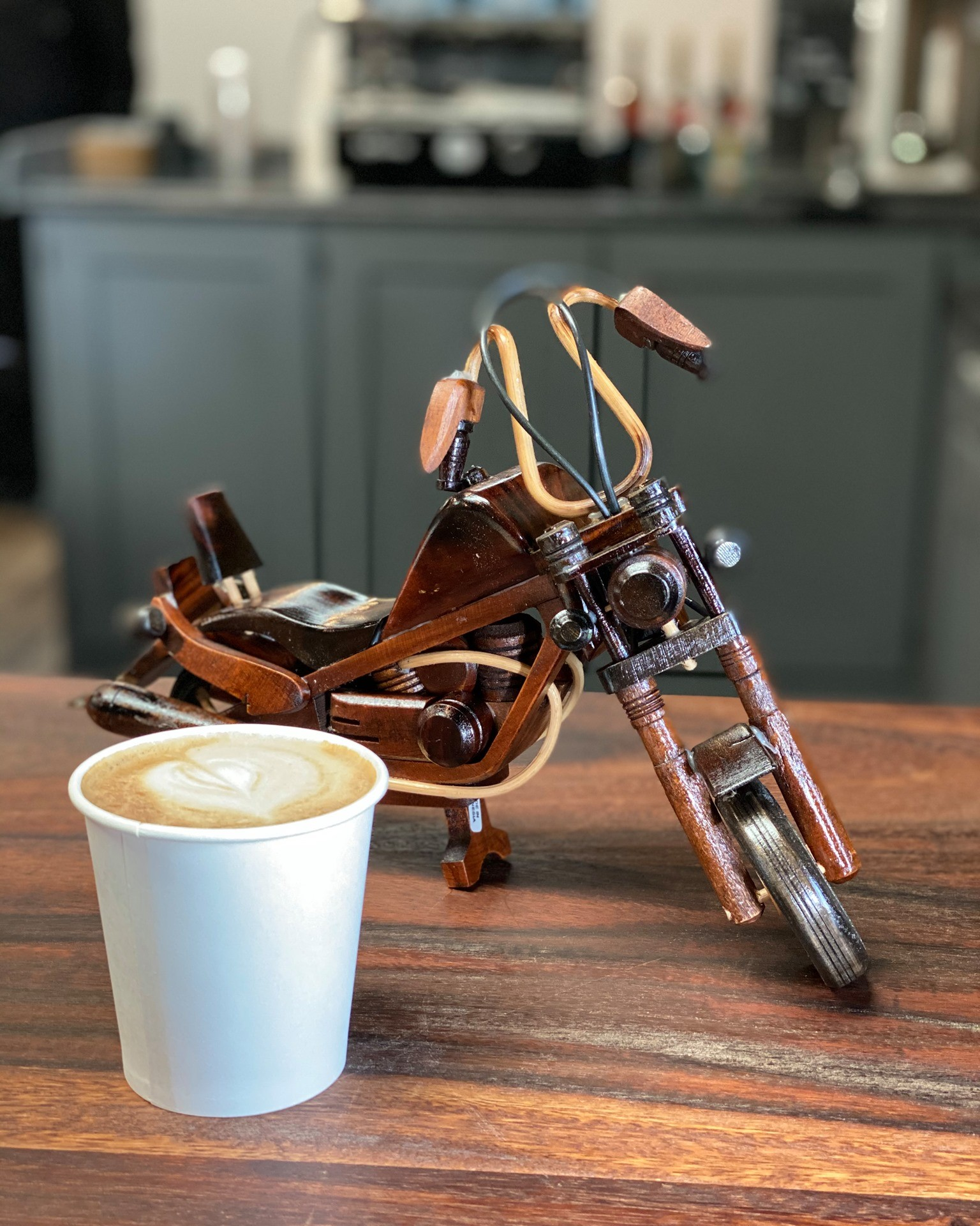 Coffee next to scale wooden motorcycle