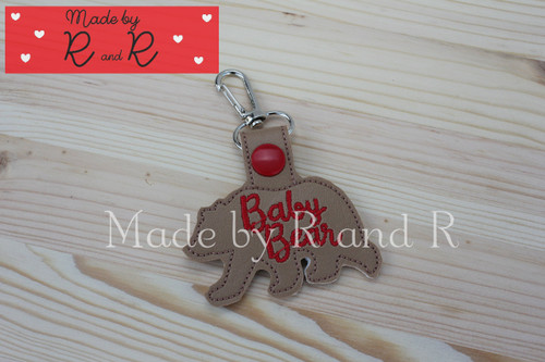 Baby bear keychain featuring brown vinyl with red lettering