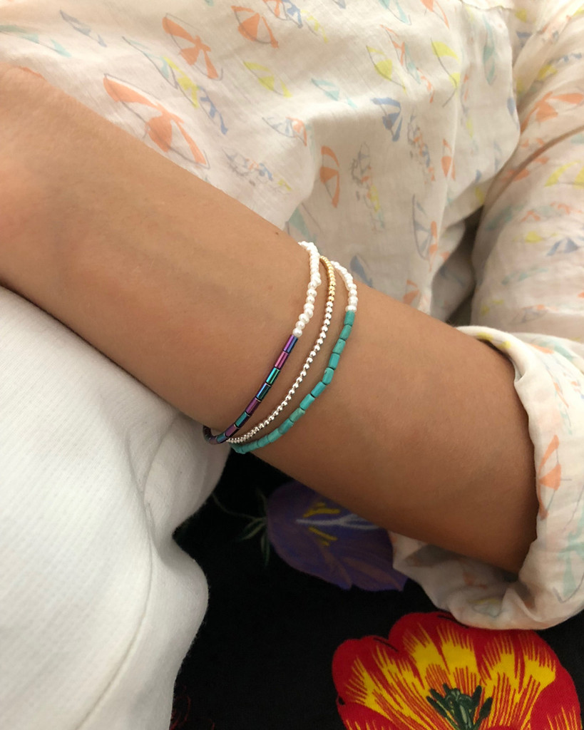 Model wearing Nektar De Stagni's colorful stretch friendship bracelet, featuring Turquoise Beads and delicate Cultured Freshwater Seed Pearls.