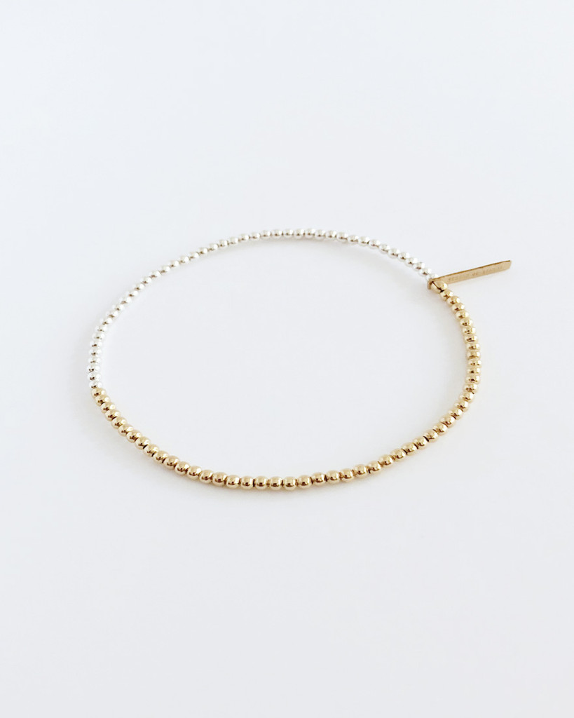 Side View of  Jewelry Designer Nektar De Stagni's minimal stretch friendship bracelet, featuring classic precious metals Gold and Silver.