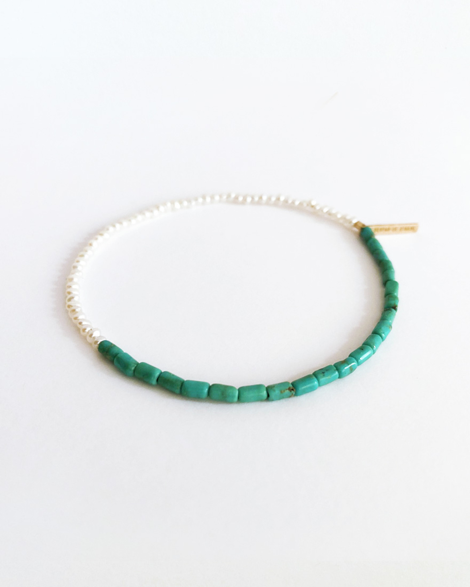 Side View of  jewelry Designer Nektar De Stagni's colorful stretch friendship bracelet, featuring Turquoise Beads and delicate Cultured Freshwater Seed Pearls.